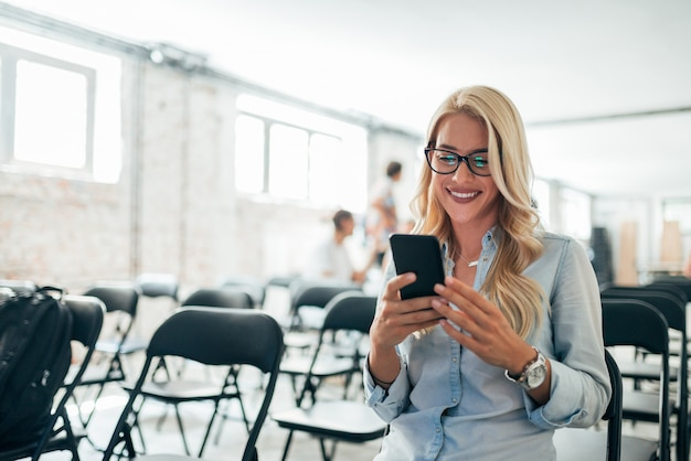 Close-up image of charming blonde woman using cellphone in conference hall.