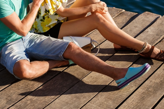 Close up image of couple sitting on the pier at romantic date, focus on legs.