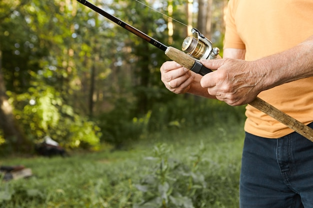 Close up image of elderly man's hands with wrinkles holding fishing rod. cropped picture of unrecognizable senior mature male fishing on river bank, standing against green trees