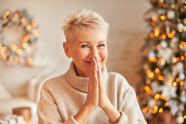 Close up image of fashionable blonde middle aged lady with pixie hairdo posing in cozy room decorated with garland making new year's resolution or making wish, holding hands pressed together