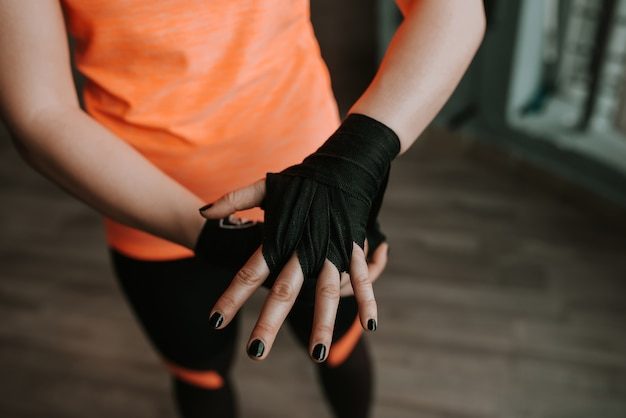 Close-up image of female hand with black strap. preparing for boxing.