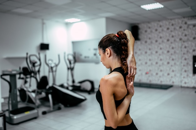 Close-up image of fit woman stretching arms at the gym.