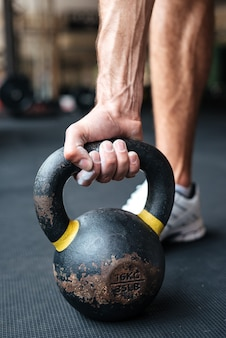 Close up image of fitness man with kettlebell in gym. preparing to raise