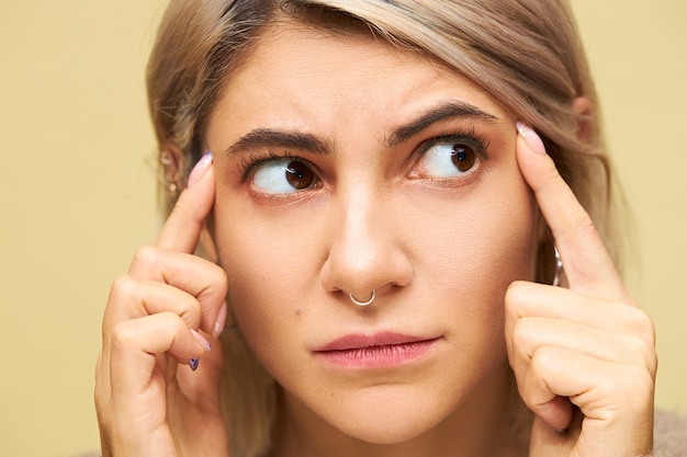 Close up image of frowning frustrated young caucasian woman holding fingers on temples thinking too hard about something, having headache or migraine. cute displeased girl saying use your brain