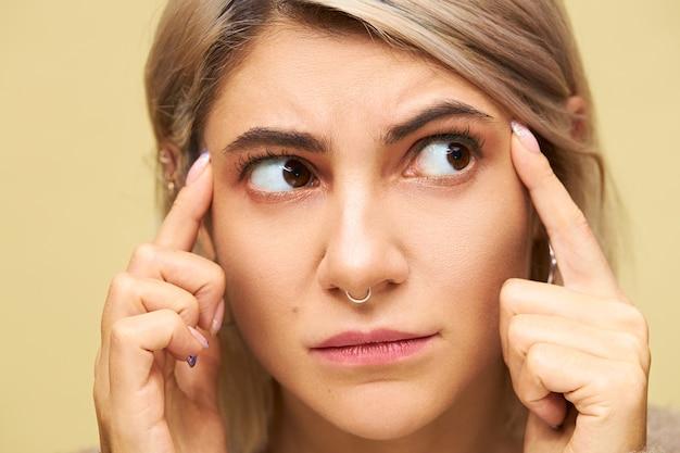 Chiuda sull'immagine di giovane donna caucasica frustrata accigliata che tiene le dita sulle tempie pensando troppo a qualcosa, avendo mal di testa o emicrania. ragazza carina dispiaciuta dicendo usa il tuo cervello