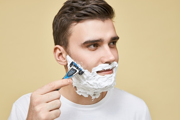 Close up image of good looking young brunette male holding razor stick using light gentle strokes while shaving beard in direction as his hair grows, having pleased facial expression, enjoying process