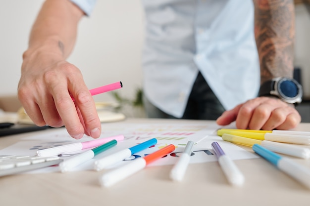 Close-up image of graphic designer using felt tip pens of various color when coloring logo mockup