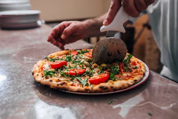 Close-up image of hand of chef baker cutting pizza.