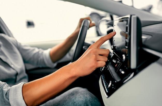 Крупным планом изображение руки человека с помощью навигационной системы во время вождения автомобиля.