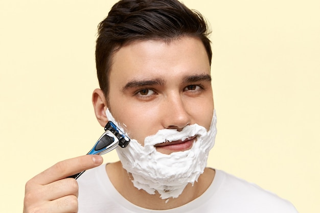 Close up image of handsome young dark haired man with white foam on his face, shaving with grain holding disposable safety razor.