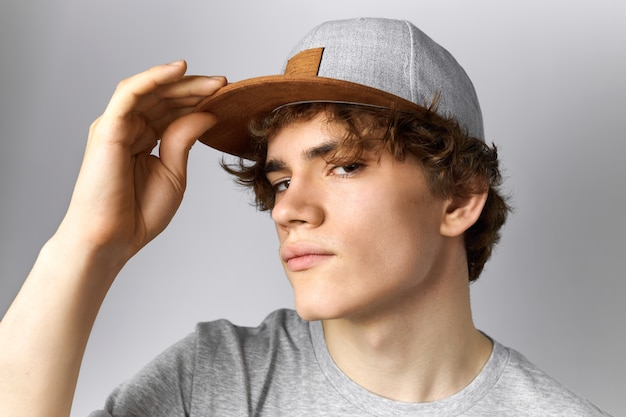 Close up image of handsome young european guy with curly hair and smooth face having fun wearing trendy snapback holding hand on peak and staring at camera with confident look. style and clothing