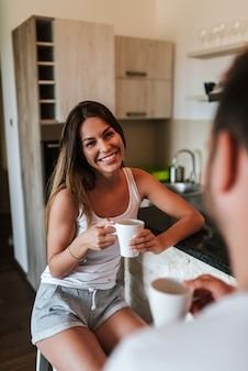 Close-up image of happy couple drinking morning coffee in the kitchen.