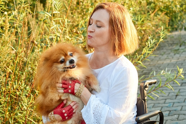 Close-up image happy red-haired woman in a wheelchair for a walk with her dog. international day of people with disabilities