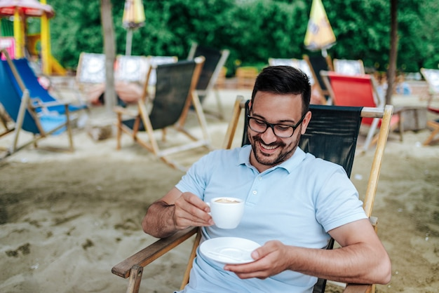 Close-up image of happy young man drinking coffee at the beach bar.