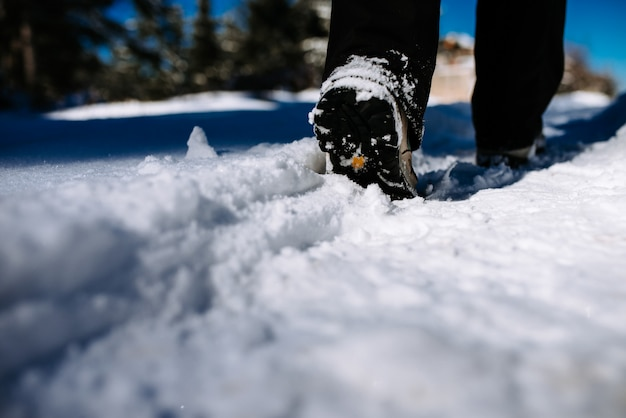 Close-up image of hiker walking on mountain covered with snow.