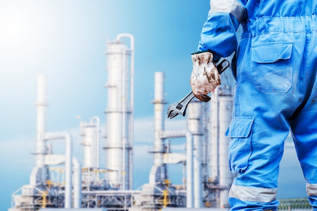 Close-up image of human hand holding wrench oil refinery distillation towers background
