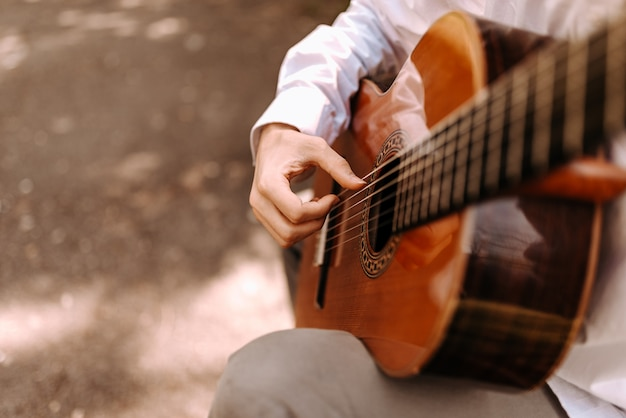 Close up image of man playing acoustic guitar outdoors.