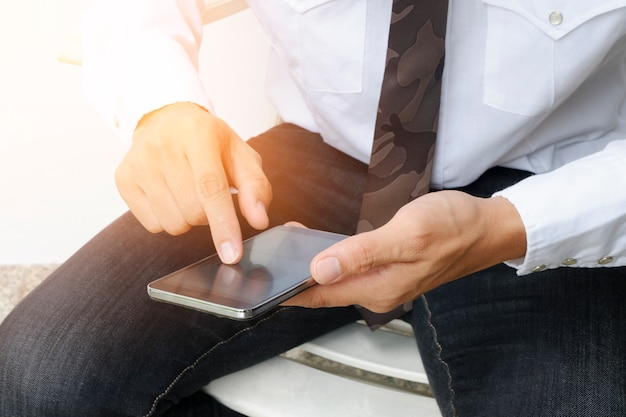 Close up image of man`s hand is touching finger of mobile phone screen