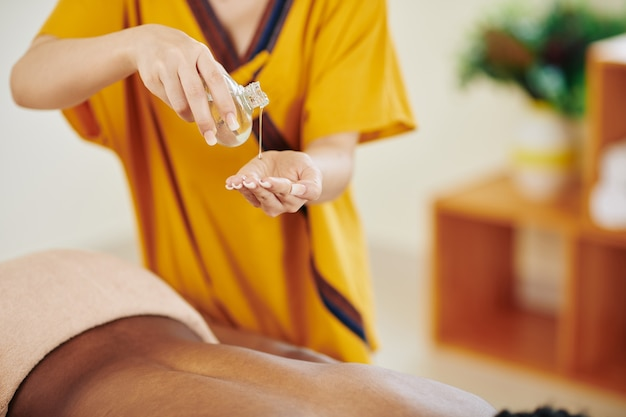 Close-up image of masseur pouring organic oil in hand to warm it up before massaging back of young woman