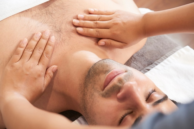 Close-up image of masseuse massaging chest and shoulders of young calm man in spa salon