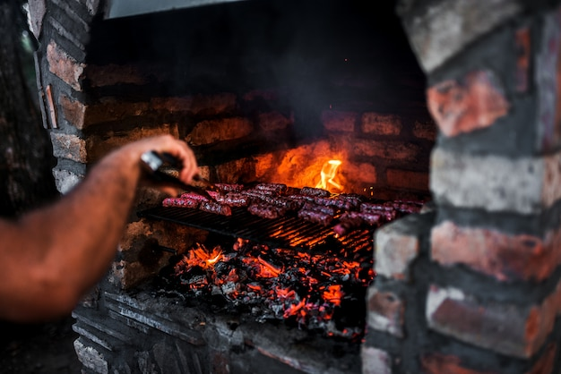 Close-up image of meat kebab cooking on a stone fireplace grill.