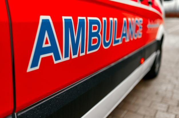 Крупным планом вид сбоку машины 911 скорой помощи. у поликлиники припаркована скорая помощь.