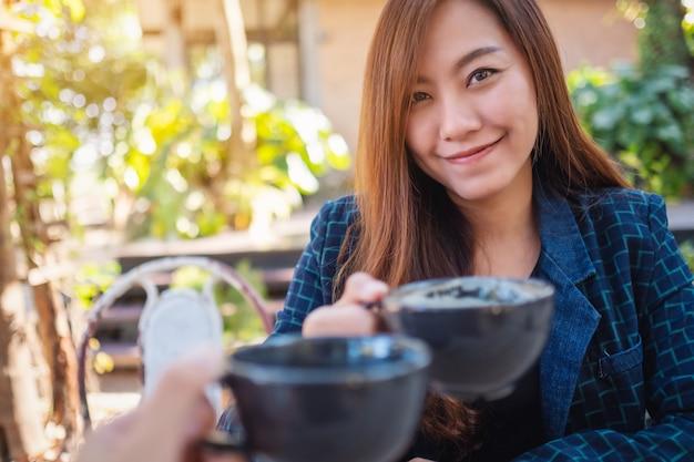 カフェで友人とコーヒーマグカップをチリンと鳴らす美しいアジアの女性の画像を閉じる