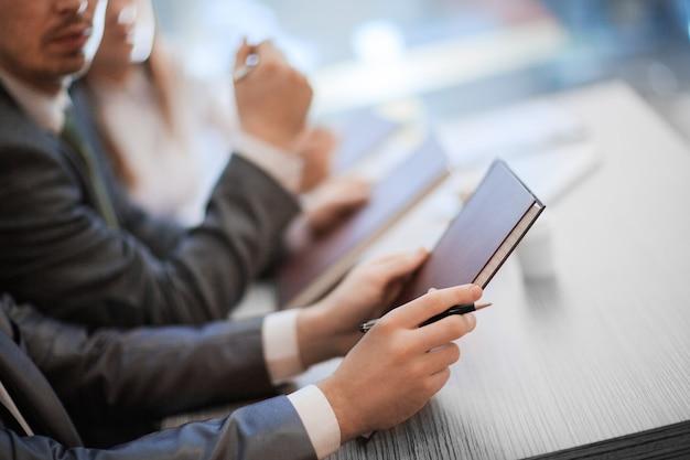 閉じる。仕事の会議でテーブルに座っている同僚の画像。ビジネスコンセプト。