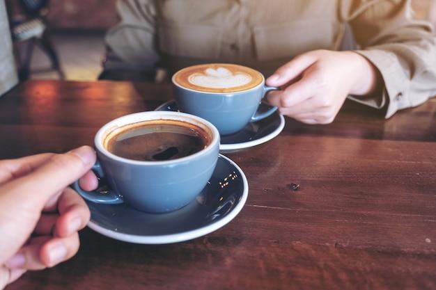Крупным планом изображение мужчины и женщины, звенящих голубыми кофейными кружками на деревянном столе в кафе