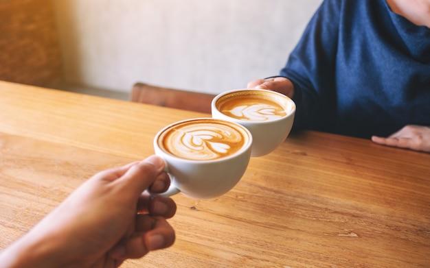 카페의 나무 테이블에 두 개의 커피 머그를 부딪치는 남자와 여자의 이미지를 닫습니다