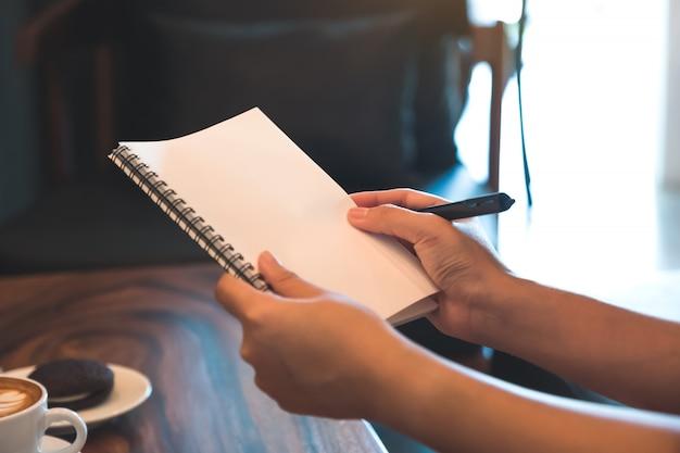 カフェで白い空白のノートブックを押しながら書き留める女性の手の画像を閉じる