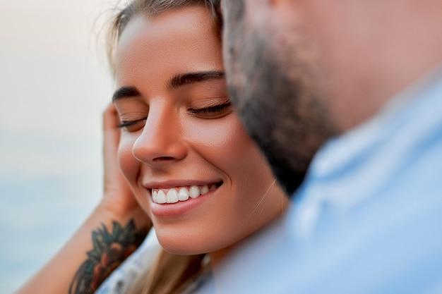 彼女の夫またはボーイフレンドの腕の中でロマンチックに海岸で時間を過ごしている魅力的な白人女性のクローズアップ画像。休暇中の愛情のあるカップル。