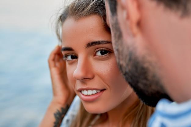Изображение крупным планом привлекательной кавказской женщины на руках у мужа или парня, романтически проводящей время на берегу моря. влюбленная пара в отпуске.