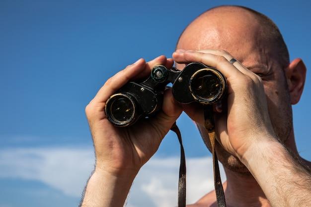 青い曇り空で双眼鏡を使用して見ている、または見ているハゲ男の手の画像をクローズアップします。