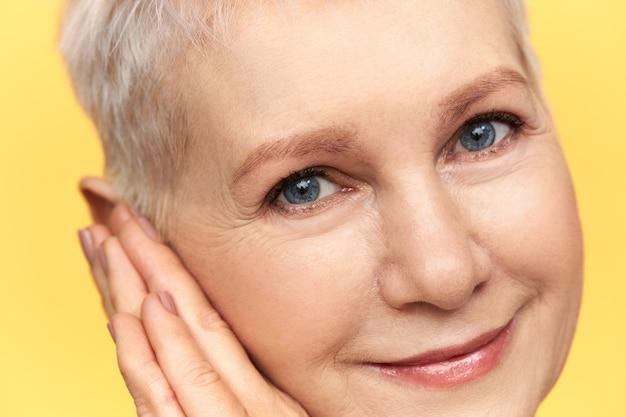 파란색 짧은 금발 머리와 미소, 뺨 아래 손을 배치 그녀의 파란 눈 주위에 주름을 가진 아름 다운 중간 나이 든된 여자의 이미지를 닫습니다.