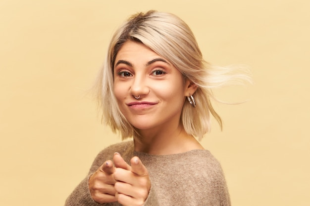 乱雑なブロンドの髪と鼻ピアスが笑顔で前指を指して、あなたに挑戦を投げている美しいかわいい女の子の画像を閉じます。ボディーランゲージ、記号、記号、ジェスチャーの概念