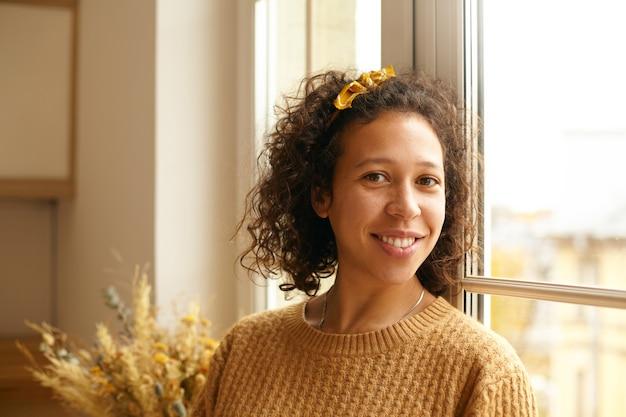 Крупным планом изображение красивой молодой женщины смешанной расы в вязаном свитере и повязке на голову, наслаждающейся утром выходного дня дома