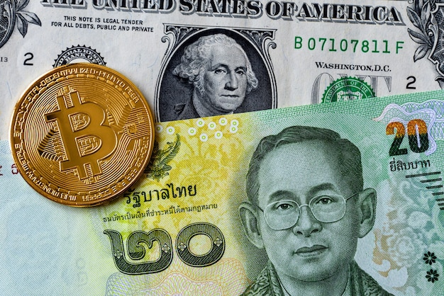 Крупным планом изображение монеты криптовалюты биткойн с банкнотами валюты таиланд бат