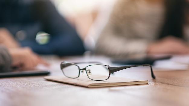 オフィスでぼやけたビジネスマンとノートブック上の黒い眼鏡の画像をクローズアップ
