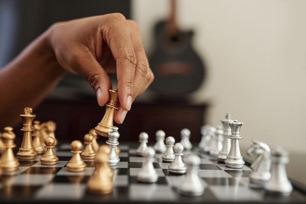 골든 퀸 체스 조각을 움직이는 흑인 남자의 클로즈업 이미지