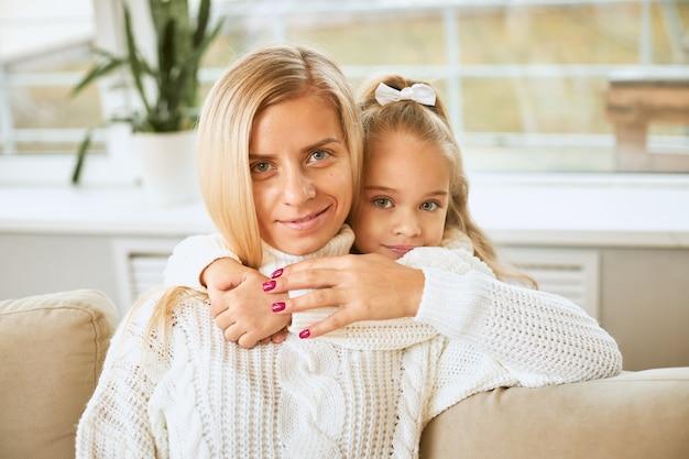 즐거운 미소로 그녀의 목에 팔을 유지하는 아름다운 젊은 어머니를 포용하는 푸른 눈의 매력적인 아기 소녀의 이미지를 닫습니다