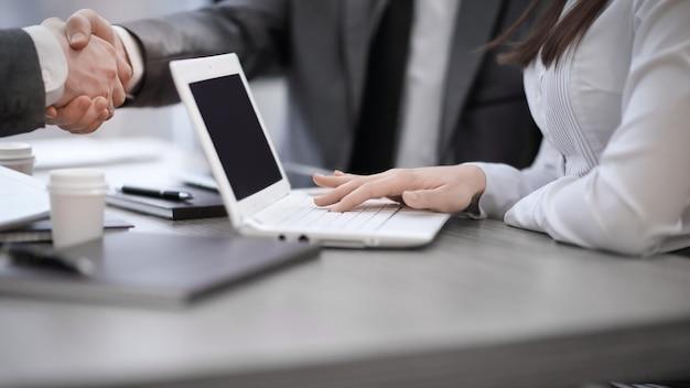 회의 또는 협상 중에 사무실 책상 위에 악수하는 비즈니스 파트너의 이미지를 닫습니다.