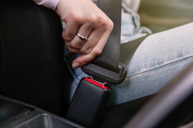 Крупным планом изображение деловой женщины, сидящей в машине, надевая ремень безопасности Premium Фотографии