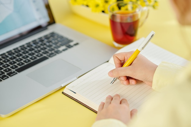Изображение крупным планом бизнесмена, пишущего мысли и идеи в планировщике при работе на ноутбуке за офисным столом