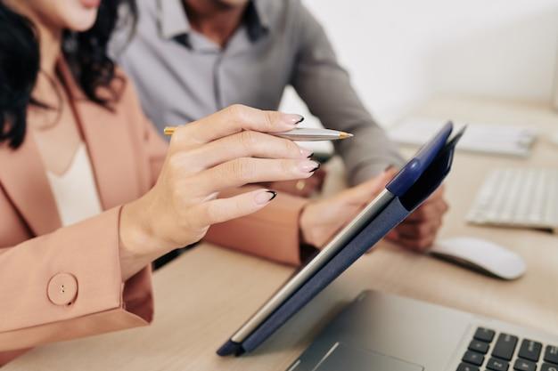 회의에서 그녀의 동료와 함께 태블릿 컴퓨터에 대한 보고서를 논의 할 때 태블릿 컴퓨터에서 가리키는 사업가의 클로즈업 이미지