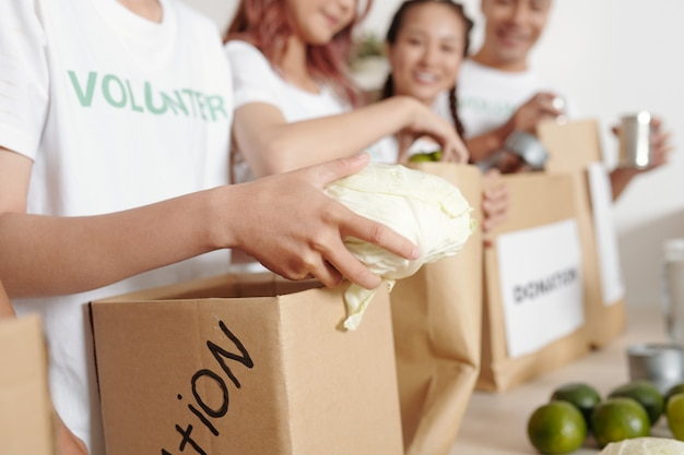 종이 패키지에 신선한 야채를 넣는 자선 단체 자원 봉사자의 클로즈업 이미지