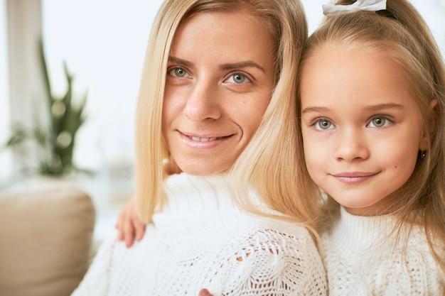 幸せな若い母親の後ろに座って、彼女のタイトな抱擁、家で一緒に素敵な時間を楽しんでいる陽気なかわいい女の赤ちゃんの画像を閉じます。人、子供時代、家族、絆と人間関係の概念