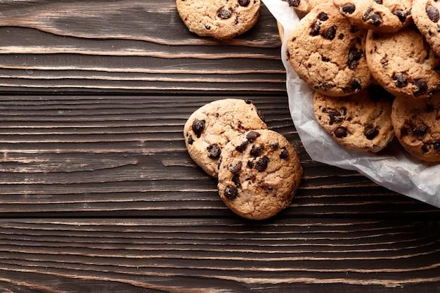 木製の背景にチョコレートチップクッキーのクローズアップ画像。テキストの場所。上面図。