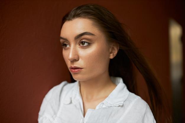 갈색 벽 배경, 주위에 그녀의 긴 느슨한 머리를 불고 바람에 걸어 흰 셔츠에 자신감이 세련 된 젊은 여성의 이미지를 닫습니다.
