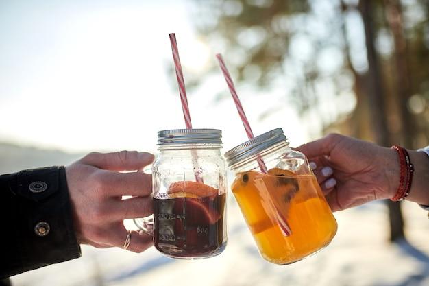 겨울 숲 앞에서 응원하고 뜨거운 mulled 와인을 마시는 부부의 이미지를 닫습니다
